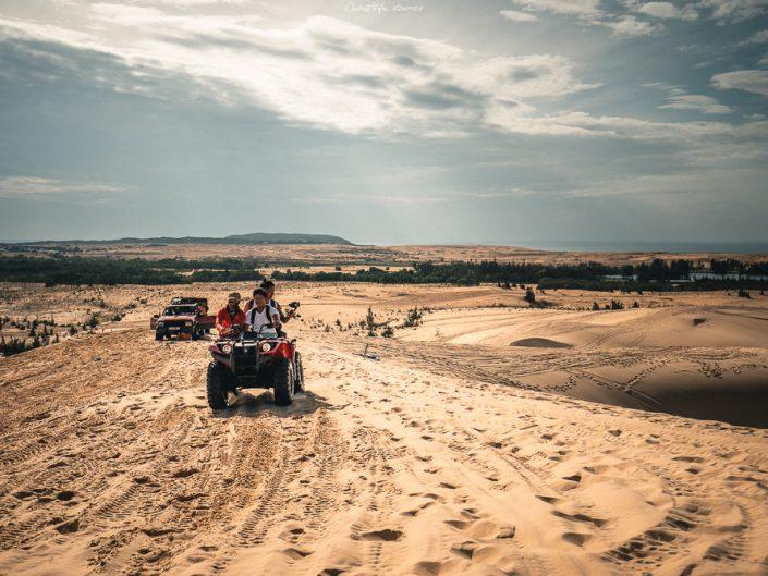 Quads düsen mit Touristen durch die Dünen