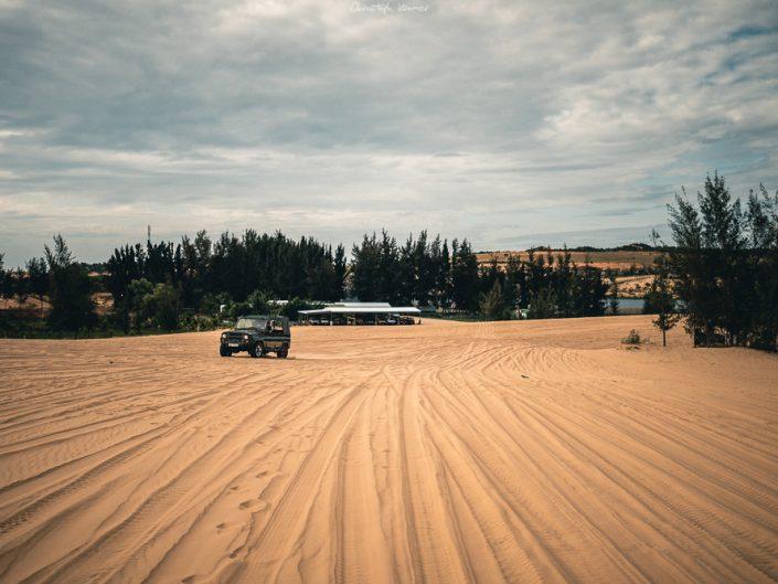 Ein Jeep fährt durch die weißen Dünen